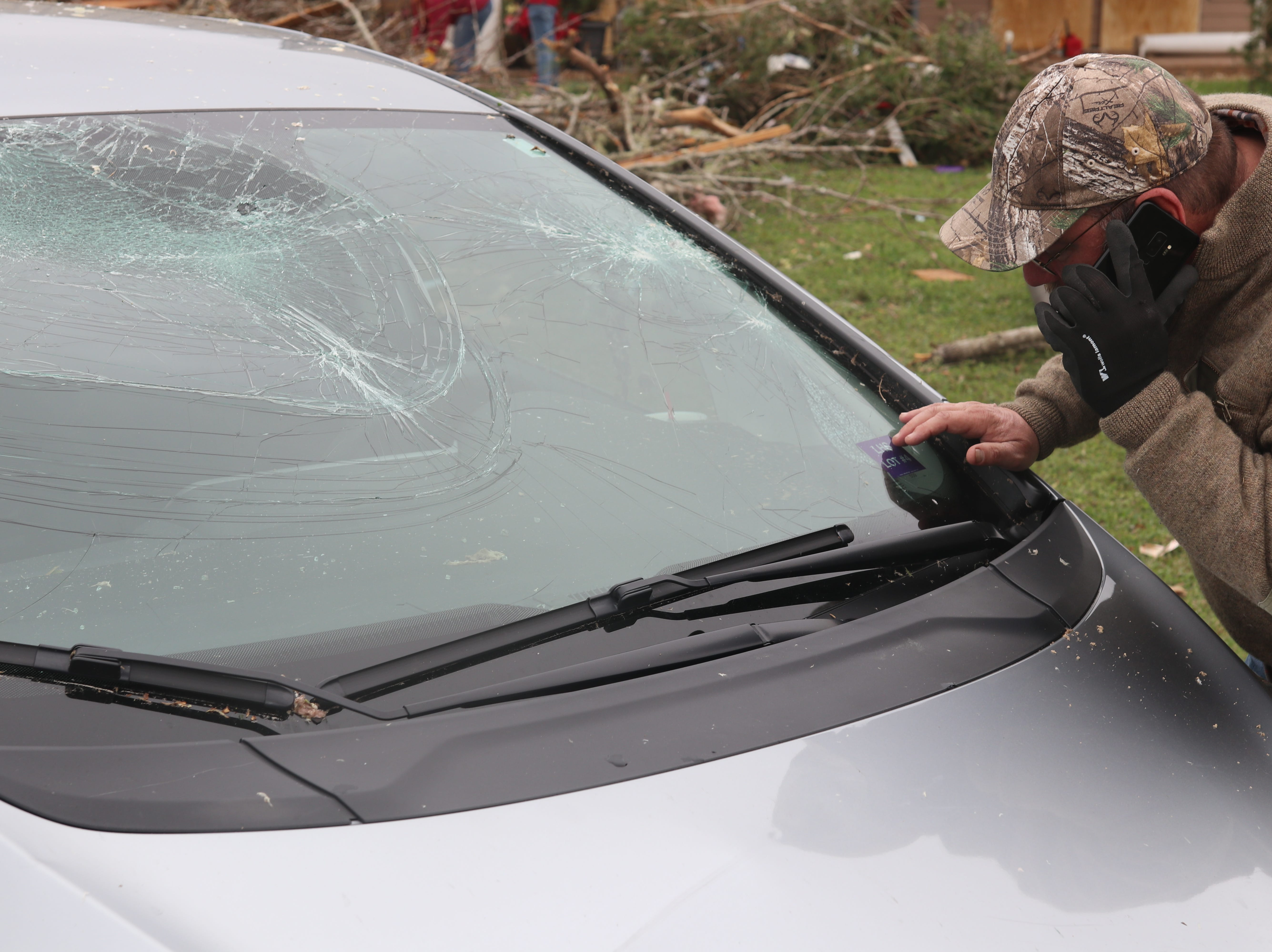 David Byler inspects a car smashed by a tree in a tornado Sunday March 3.