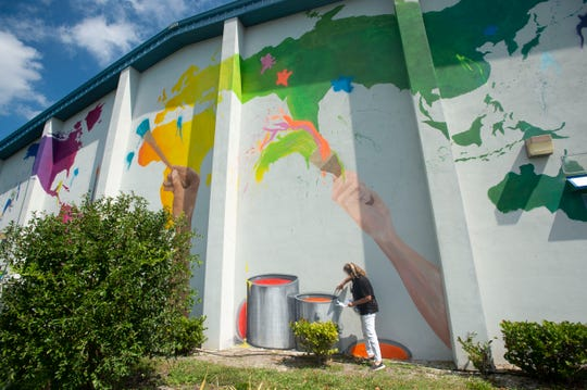 """""""I want each of the children here to know that it's up to you to create the world, to make the contribution that is uniquely yours,"""" said mural artist Nadia Utto as she continued work on """"Color the World,"""" the 24th mural created by Utto for the Hobe Sound Murals Project, on Monday, March 4, 2019 at the Boys & Girls Club of Martin County Cole-Clark Club in Hobe Sound. Children from the organization will help finish the """"monumental"""" 75' x 35' wall Friday afternoon, when they will use spray paint and brushes to add color to the wall. """"They'll get to be connected with it and do their own expressions,"""" Utto said."""