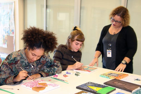 Clark Advanced Learning instructor Alexandria Gribble, right, works with students Mya DeSimone and Sophia Demiduke on entries for the March 8-28 student-driven kinetic pointillism exhibit at the Port St. Lucie Civic Center.