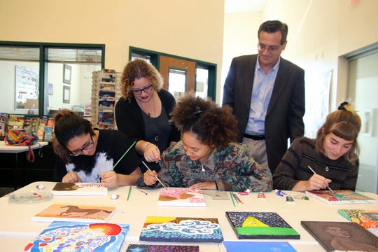 Instructor Alexandria Gribble, standing left, and artist Rob Otteson, right, look over kinetic pointillism work being created by students Crystal Aguilar, Mya DeSimone, Sophia Demiduke.