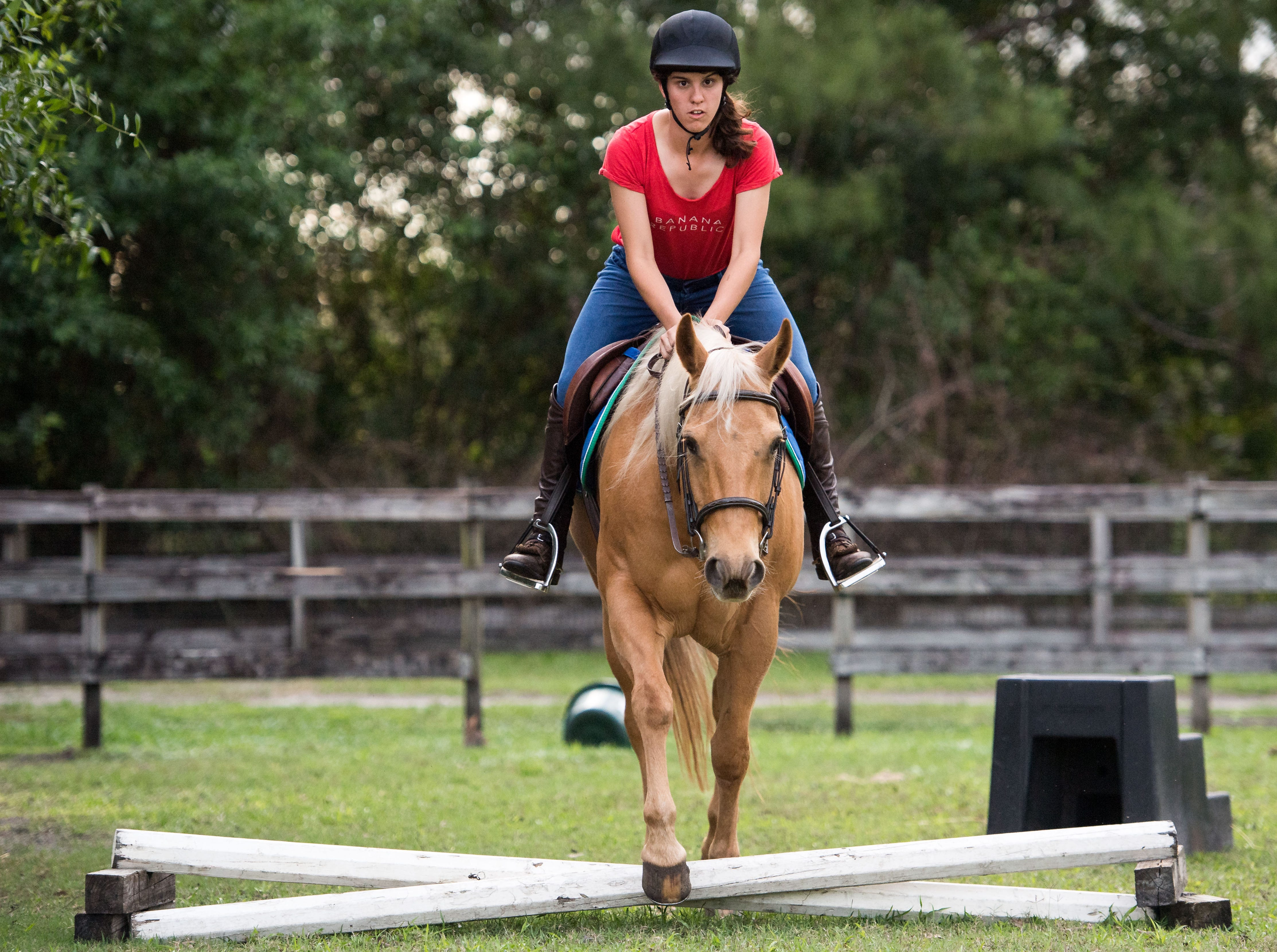 """Cori Davis, an equestrian from Palm City, rides Jaye, one of her family's horses under the watch of riding instructor Patty Nelson at Davis' home March 1, 2019, in Palm City. Davis will be traveling to Abu Dhabi, United Arab Emirates, to compete in the 2019 Special Olympics World Games, which begin March 14. """"An Emirates family is donating all the horses (for the competition),"""" Cori's mother, Jacque Lewis, said, """"so Patty's been having her on a bunch of different horses."""""""