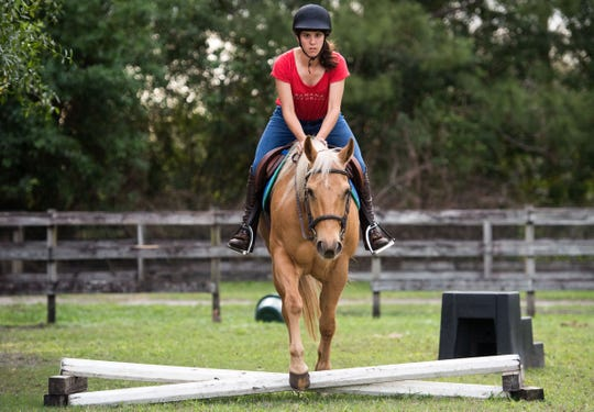"Cori Davis, an equestrian from Palm City, rides Jaye, one of her family's horses under the watch of riding instructor Patty Nelson at Davis' home March 1, 2019, in Palm City. Davis will be traveling to Abu Dhabi, United Arab Emirates, to compete in the 2019 Special Olympics World Games, which begin March 14. ""An Emirates family is donating all the horses (for the competition),"" Cori's mother, Jacque Lewis, said, ""so Patty's been having her on a bunch of different horses."""