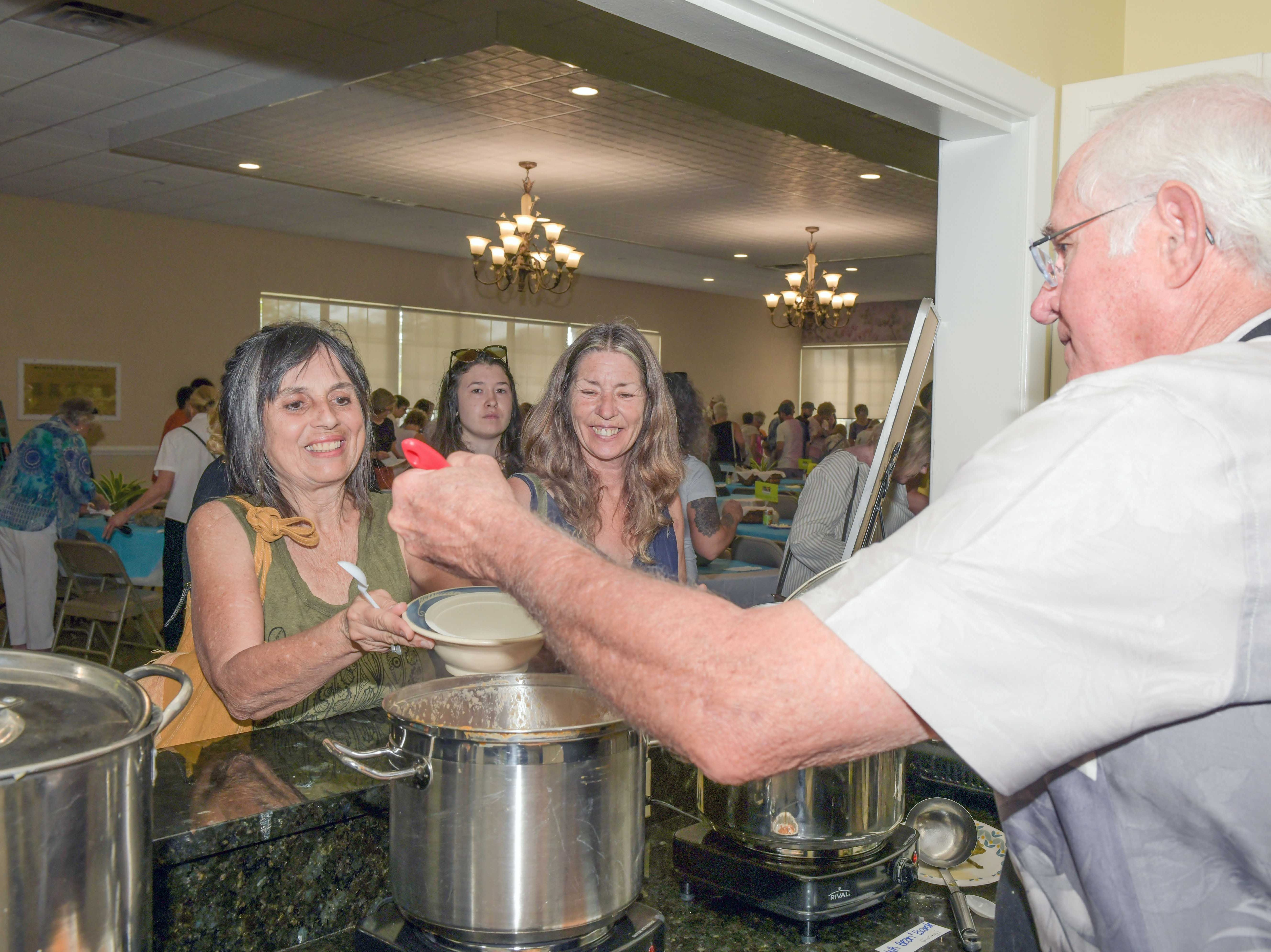 Charly Hill, left, and Pamela Ketcham are served by Craig Rich at the 13th annual Lundin Kudo Empty Bowls Project at the Woman's Club of Stuart.