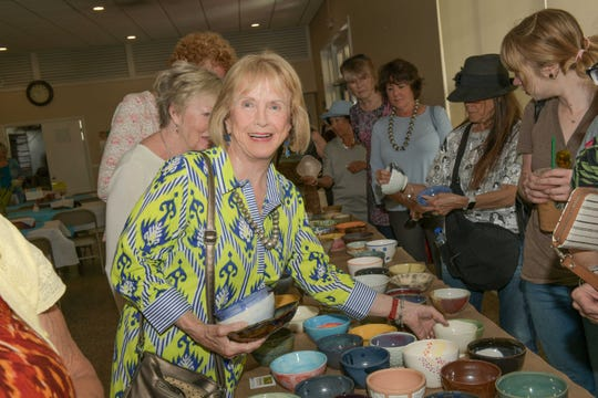 Donna McAlear likes what she sees at the 13th annual Lundin Kudo Empty Bowls Project at the Woman's Club of Stuart.