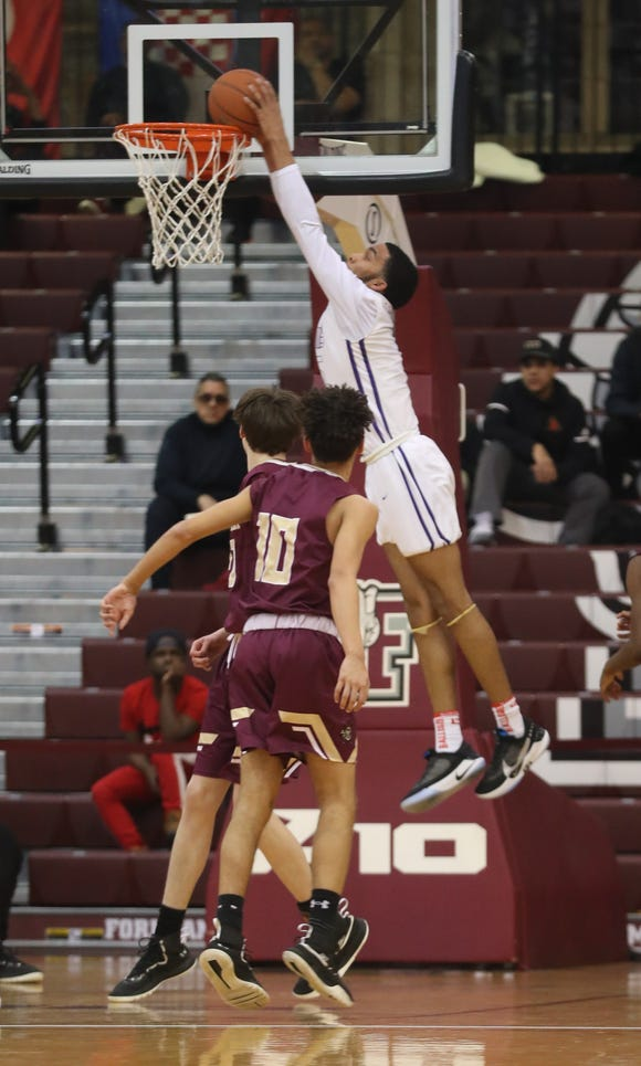 Julian Champangie of Bishop Loughlin finishes an alley-pop against Iona Prep during a Catholic High School Athletic Association basketball quarterfinal game at Fordham University in the Bronx March 3, 2019. Bishop Loughlin defeated Iona Prep 59-47.