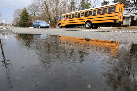 A school bus passes by melting slushy puddles on Boxwood Road in Newport.