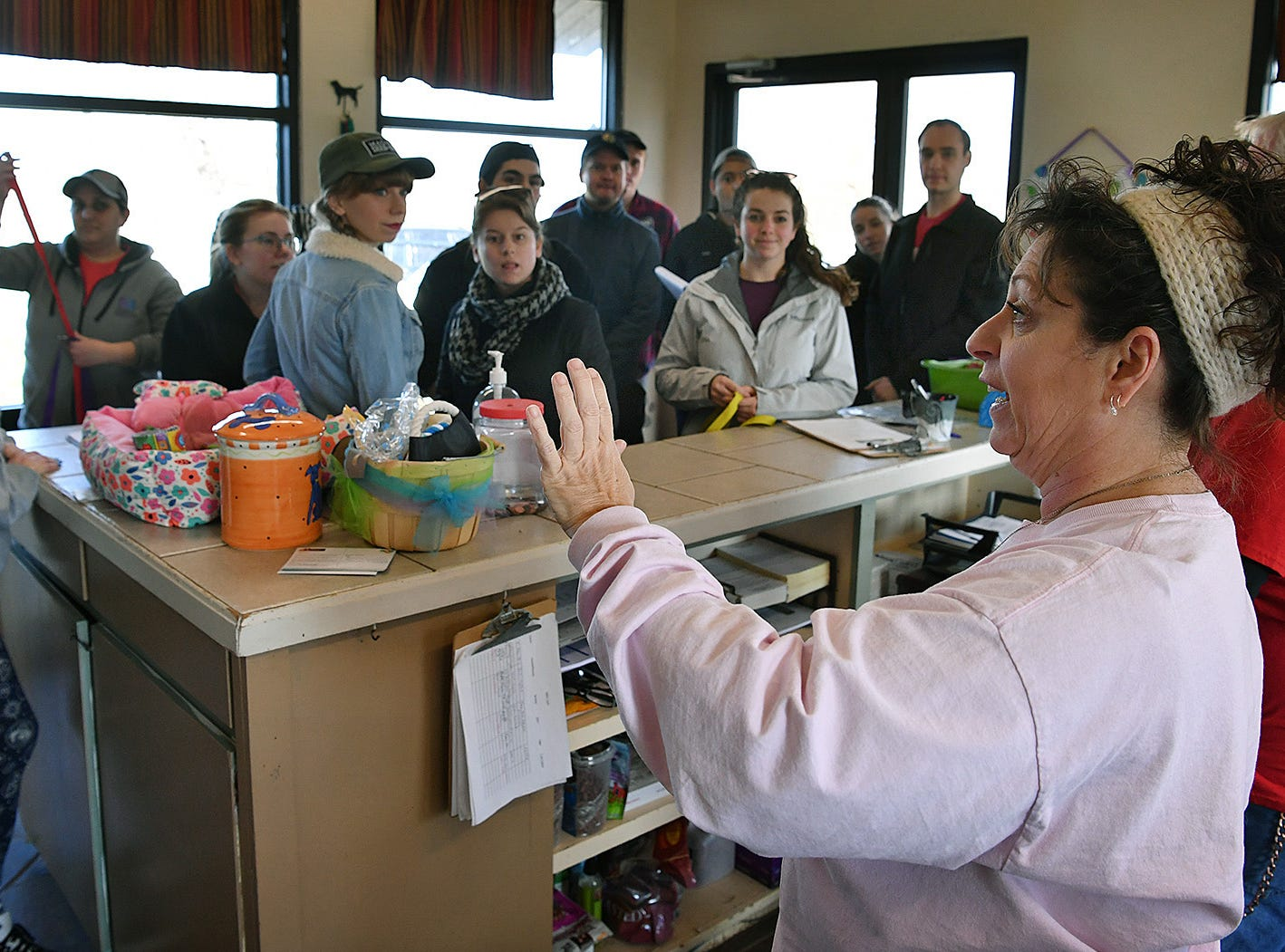 Cheryl Miller, executive director of the Humane Society of Wichita County, gives directions to cast and crew members of the show Paw Patrol, as they arrive to volunteer Monday afternoon.