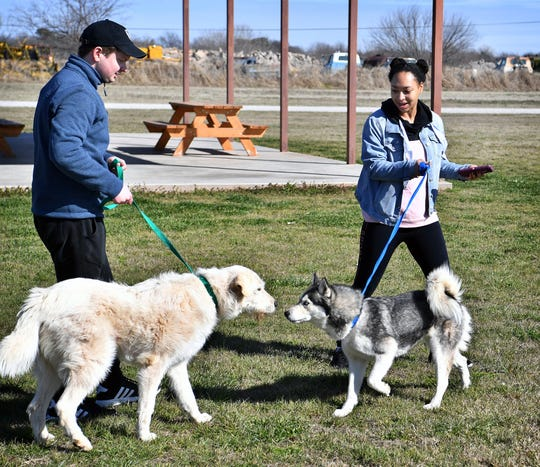 Casey Andrews and Kendra Johnson walk dogs while volunteering at the Humane Society of Wichita County Monday afternoon. Andrews plays Mayor Humdinger and Johnson is Zuma in Paw Patrol Live.