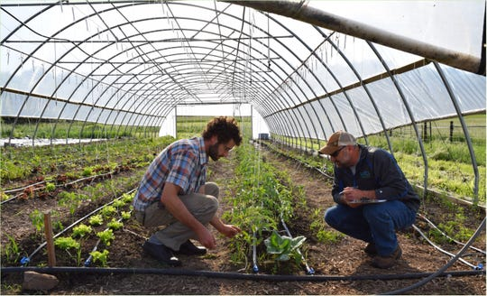 Caleb (left) and Matt Miller, NRCS Soil Conservation Technician, discuss multi-crop production with the newly installed micro irrigation.