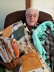 Bob with some of the cards he has received, a patchwork quilt from the HCE Country Apples and the green/grey quilt from CP Fox Cities.