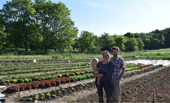 Caleb, Eva, and their son, Waylon, standing next to one of the vegetable fields.
