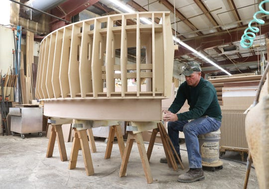Duane Murray works on a custom reception desk at Mock Woodworking in Zanesville. The company recently acquired a similar company in Indiana.