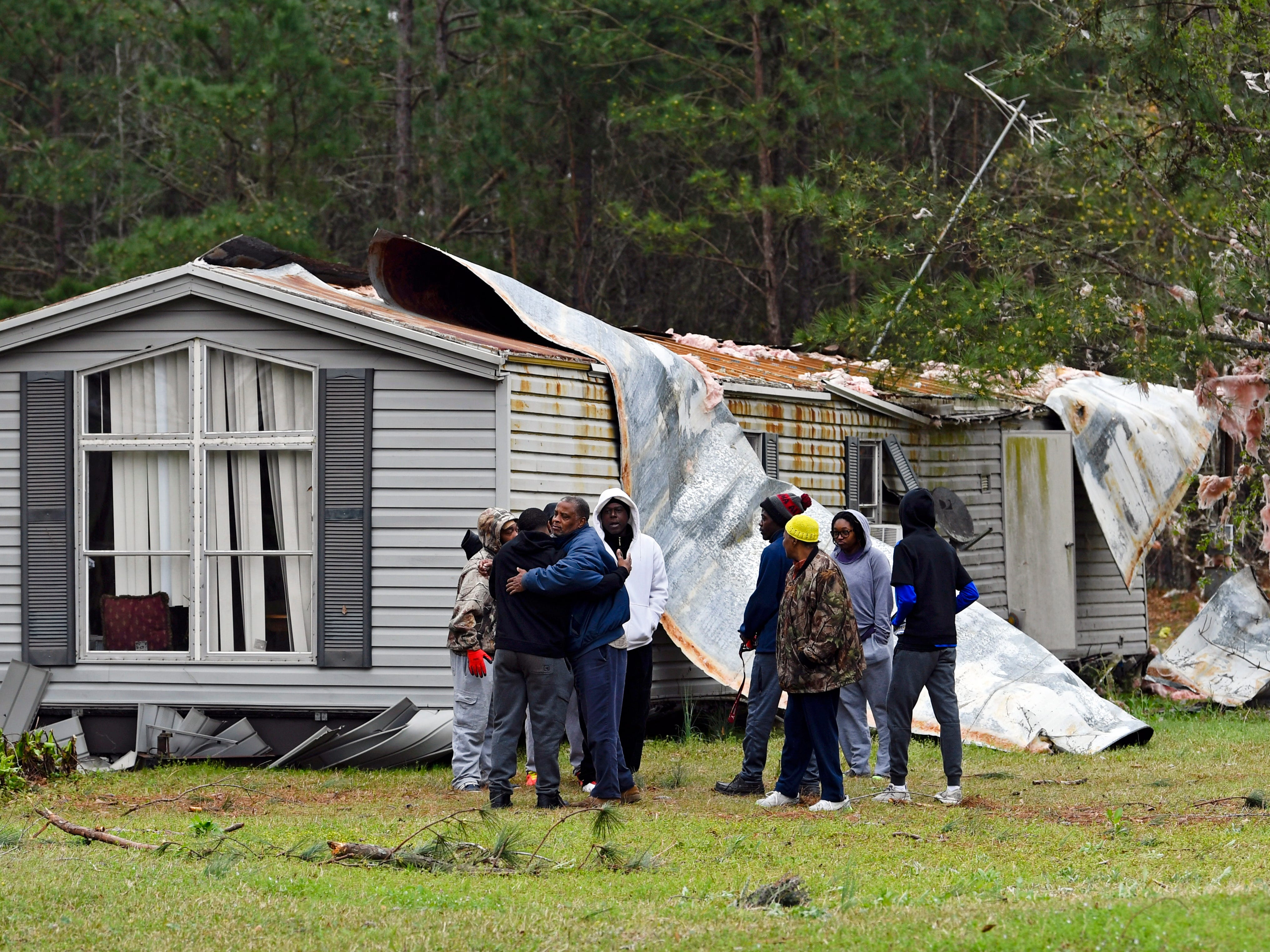 Family members console each other after a tornado damaged a home the previous day in Beauregard, Ala., March 4, 2019.   At least 23 people are confirmed dead following Sunday's tornado outbreak with violent storms that left debris strewn across southern Alabama and Georgia.