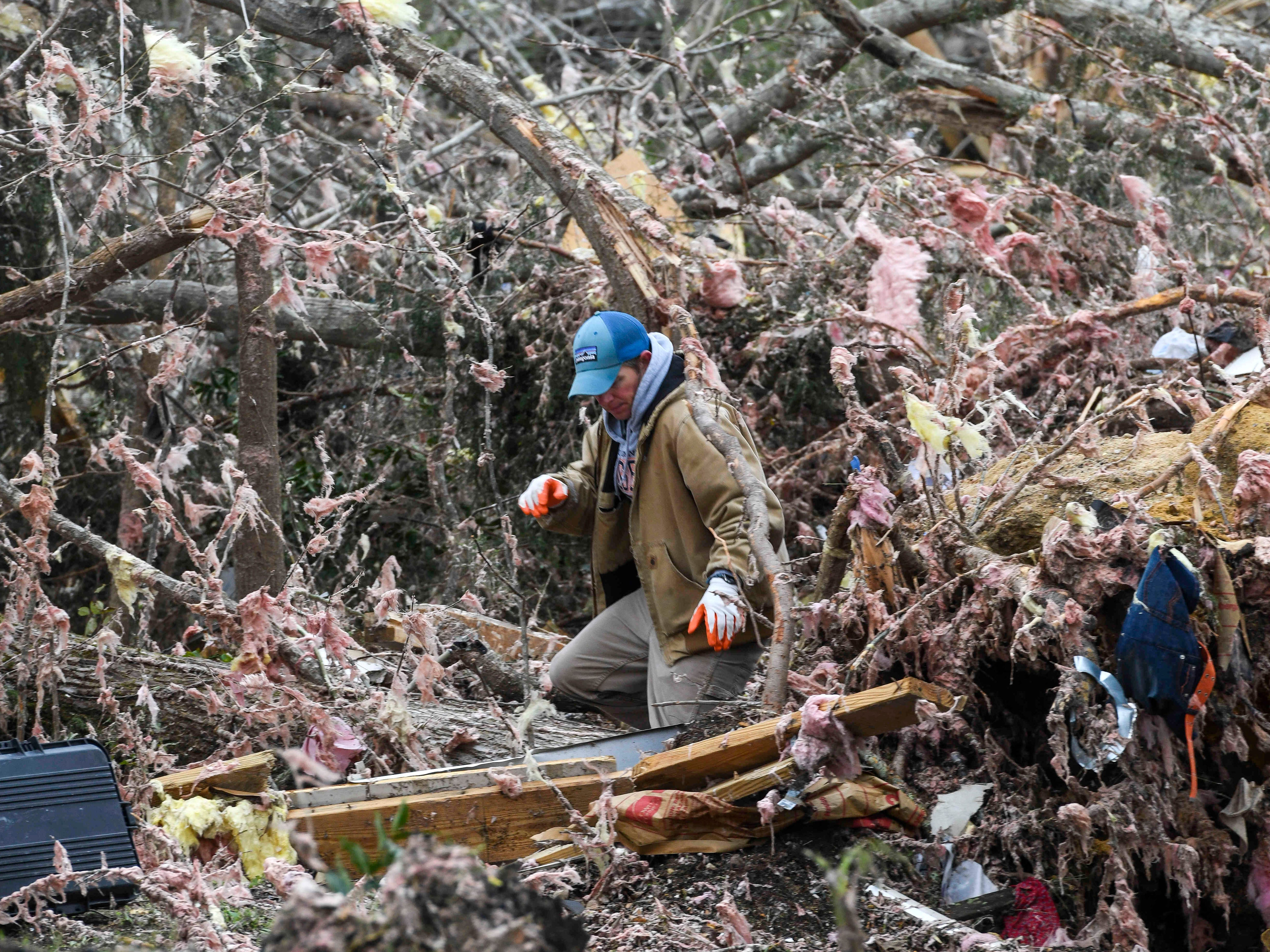 A resident looks through the debris of a family member's destroyed home the day after a deadly tornado ravaged the area, in Beauregard, Ala., March 4, 2019.