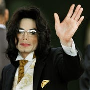 Michael Jackson waves as he arrives at the Santa Barbara County courthouse in Santa Maria, California on June 3, 2005.