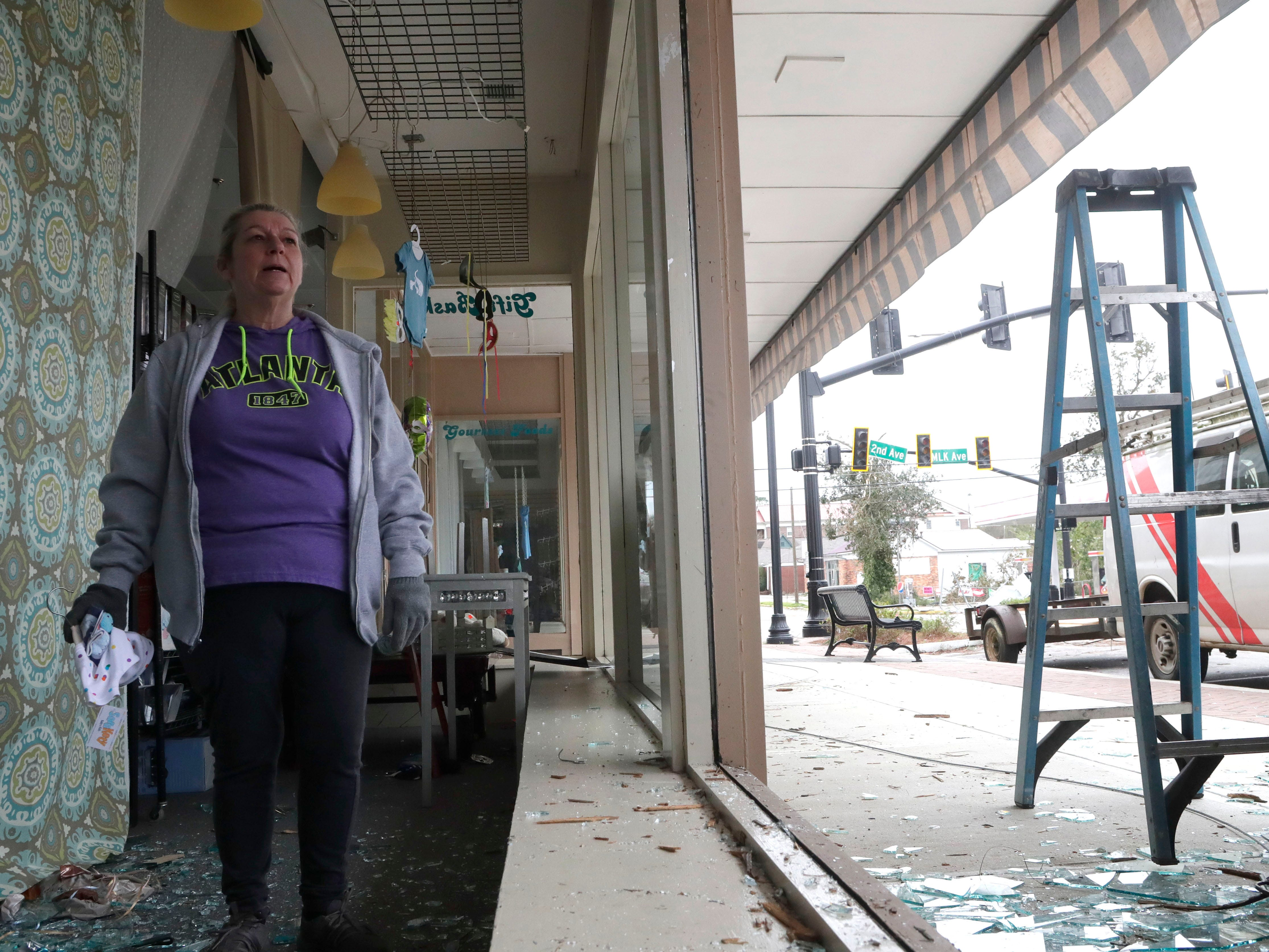 Debbi Miller, owner of Miss Myrt's in  Cairo, Ga., cleans up shattered glass on March 4, 2019.