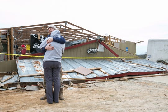 Gabe and Brandi O'Neal embrace outside of the Buck Wild Saloon after it was destroyed by a tornado March 4, 2019 in Smith Station, Ala.