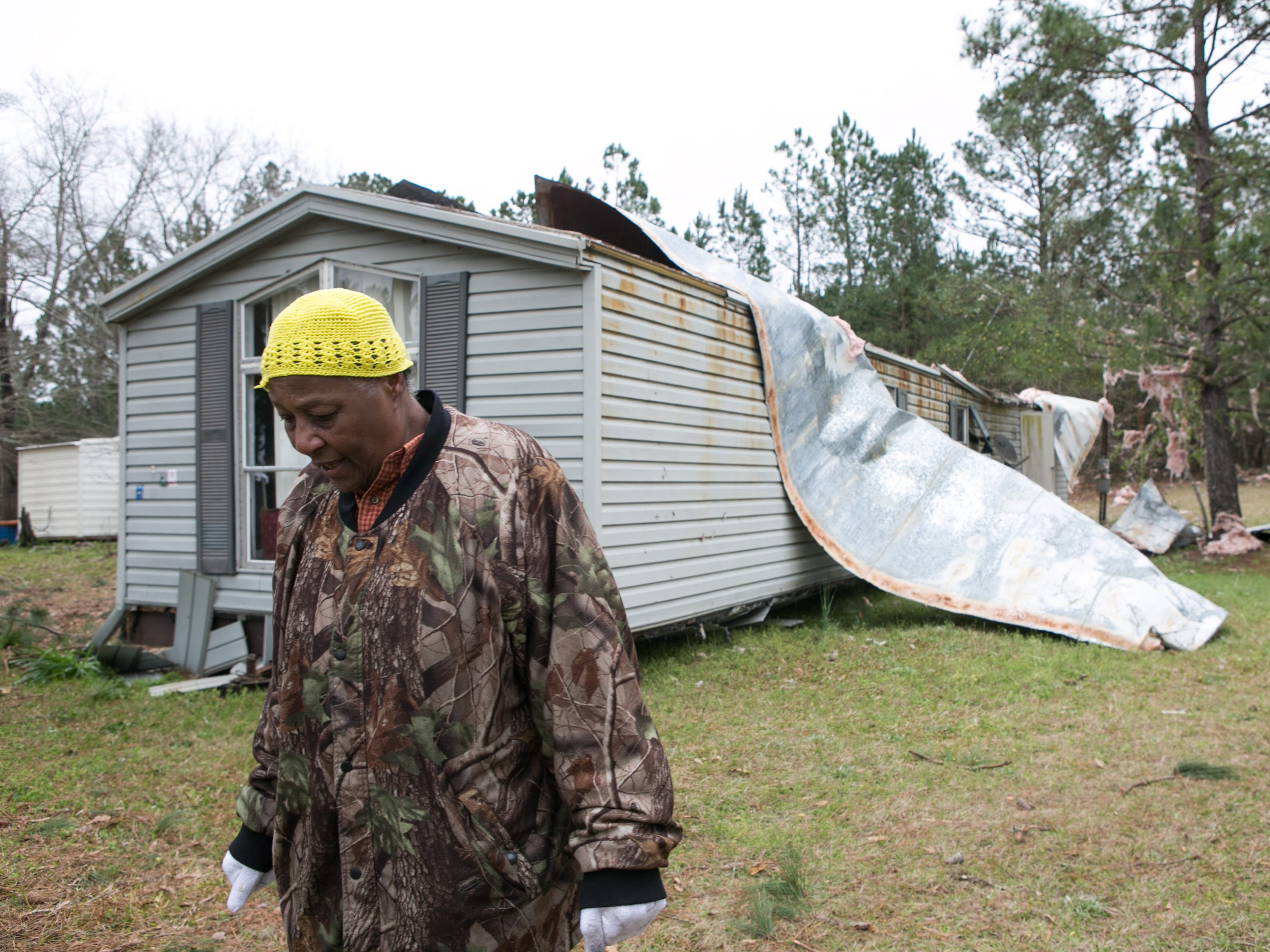 Christine Richardson stands in front of a house she owns that was damaged by a tornado outbreak on March 4, 2019 in Beauregard, Ala.  Richardson's son was in the house when the tornado hit and is safe.