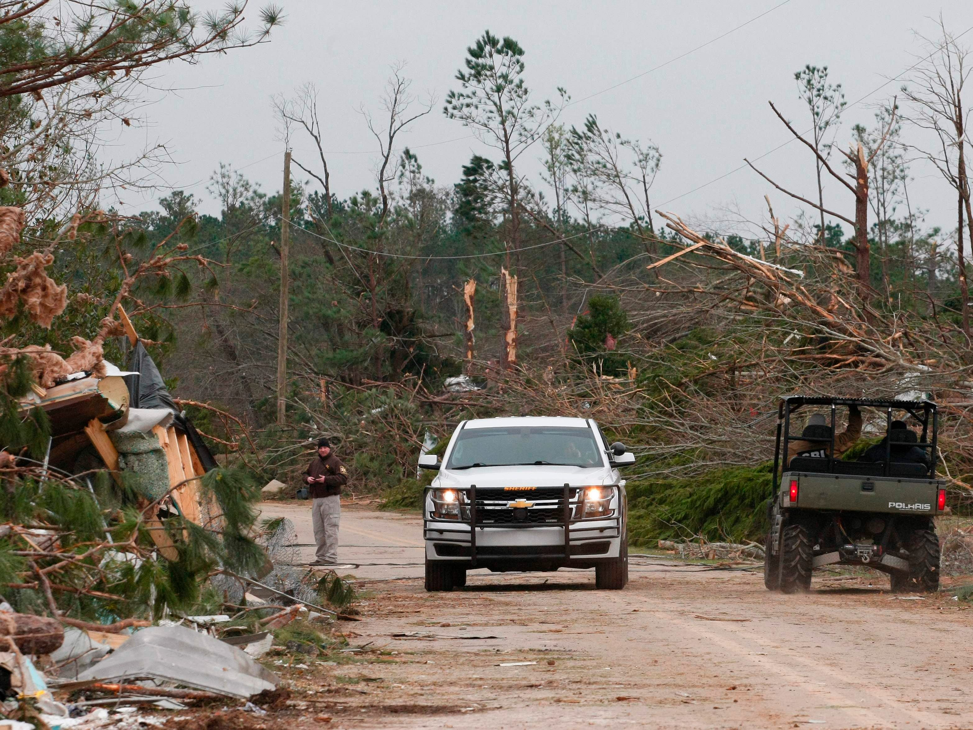 """Damage from a tornado which killed at least 23 people is seen as Lee county deputies secure the scene in Beauregard, Alabama on March 4, 2019.Rescuers in Alabama were set to resume search operations Monday after at least two tornadoes killed 23 people, uprooted trees and caused """"catastrophic"""" damage to buildings and roads in the southern US state.""""The devastation is incredible,"""" Lee County Sheriff Jay Jones told the local CBS affiliate late Sunday.""""I cannot recall at least in the last 50 years... a situation where we have had this loss of life that we experienced today."""""""