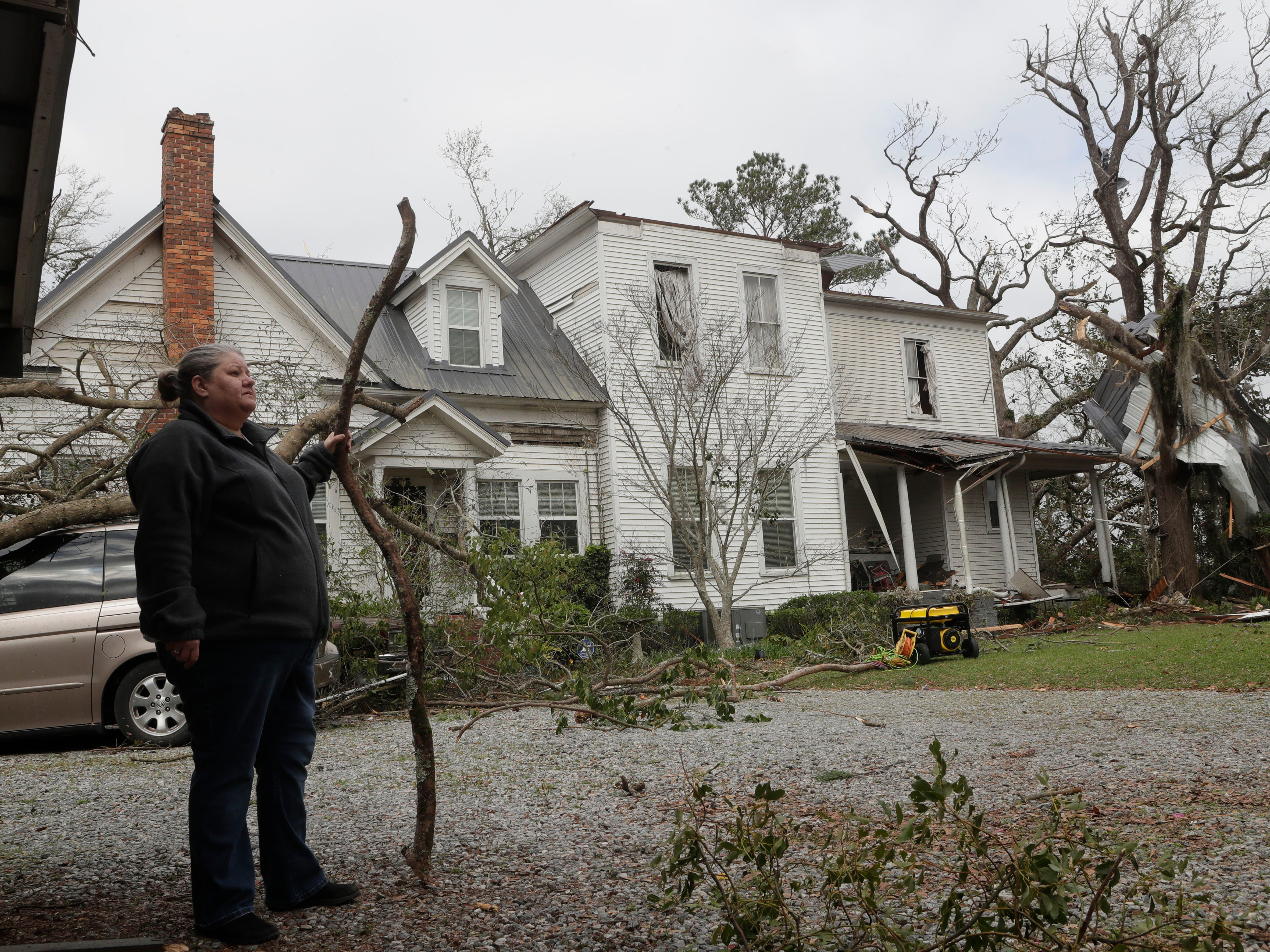 Tammy Esther, daughter of Ellen White, stands outside her mother's home and surveys tornado damage from the previous night on March 4, 2019.