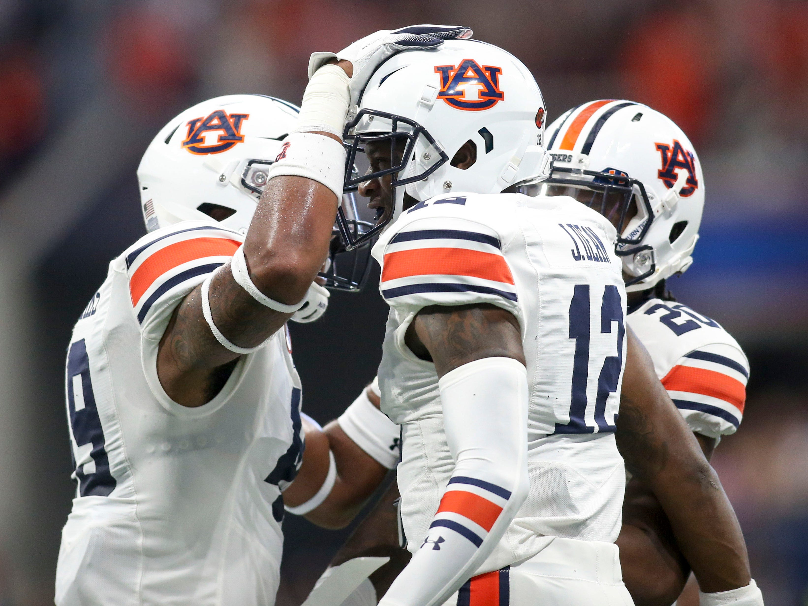Auburn Tigers defensive back Jamel Dean (12) celebrates after an interception with linebacker Darrell Williams (49) and defensive back Jeremiah Dinson (20) against the Washington Huskies in the first quarter at Mercedes-Benz Stadium.