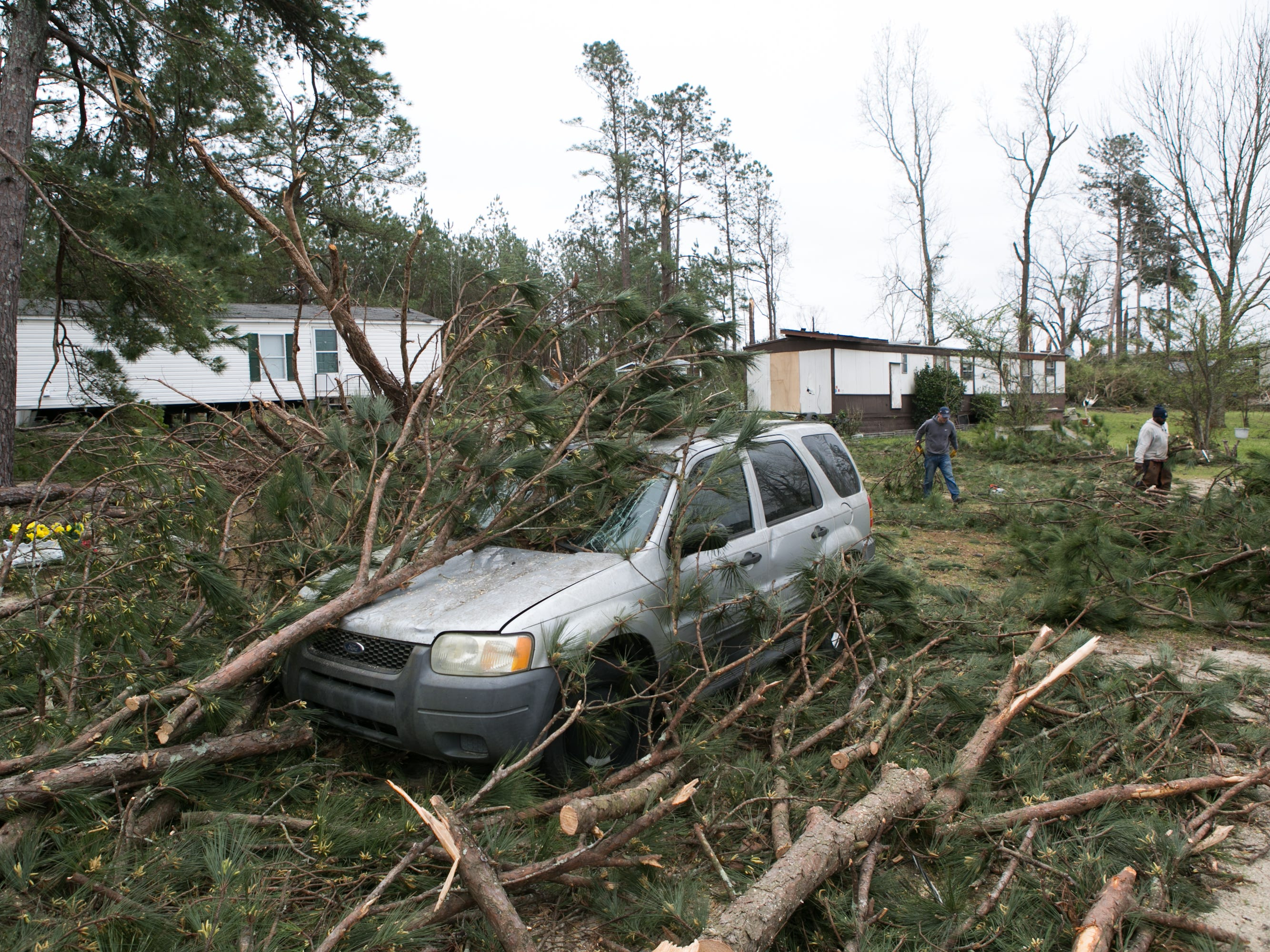 Volunteers and residents clean up trees and debris from a tornado at a home on March 4, 2019 in Beauregard, Ala.