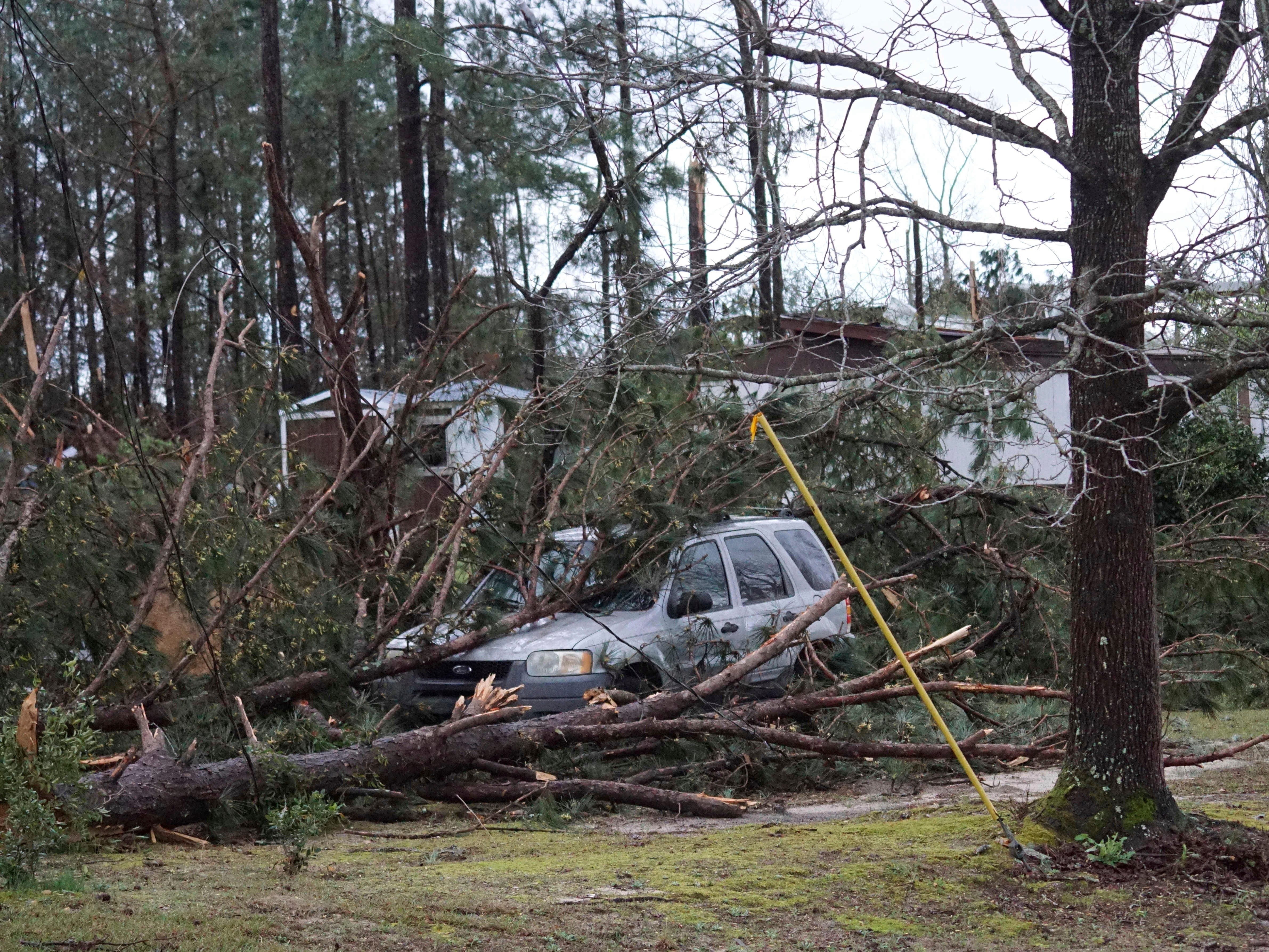 A vehicle is caught under downed trees along Lee Road 11 in Beauregard, Ala., Sunday, March 3, 2019, after a powerful storm system passed through the area. (Kara Coleman Fields/Opelika-Auburn News via AP) ORG XMIT: ALOPE131