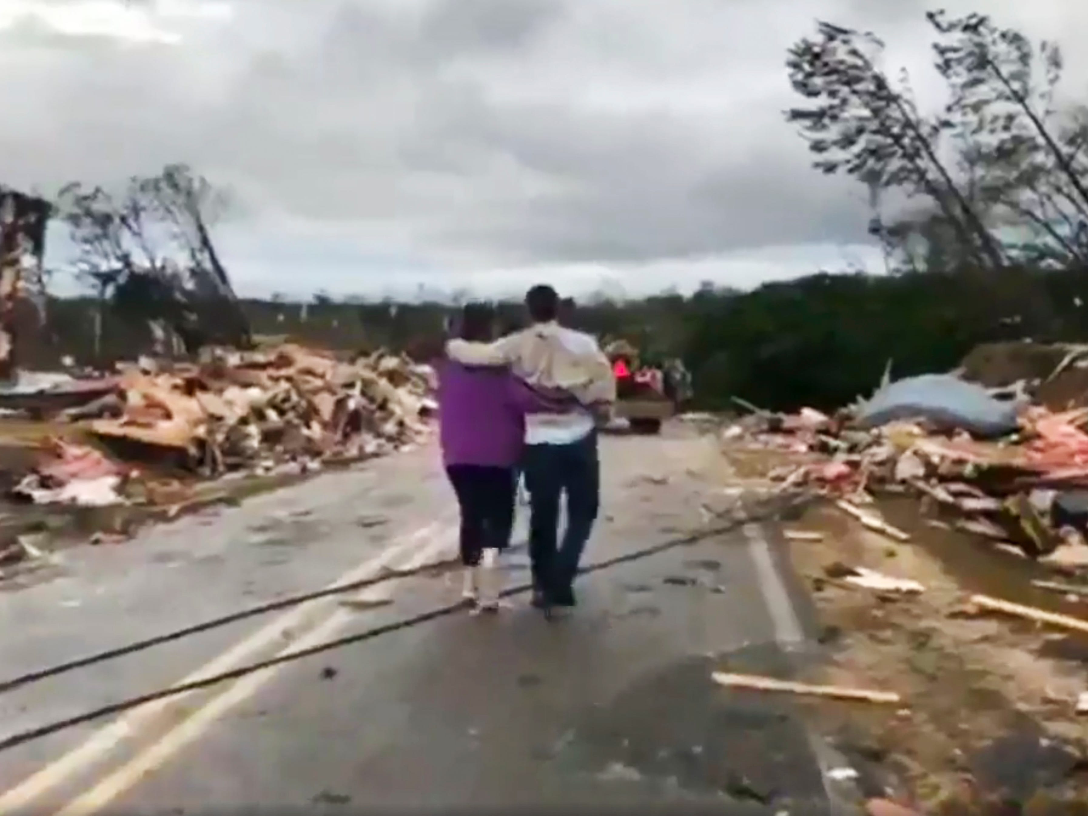 People walk amid debris in Lee County, Ala., after what appeared to be a tornado struck in the area Sunday, March 3, 2019. Severe storms destroyed mobile homes, snapped trees and left a trail of destruction amid weather warnings extending into Georgia, Florida and South Carolina, authorities said. (WKRG-TV via AP) ORG XMIT: WKRG701