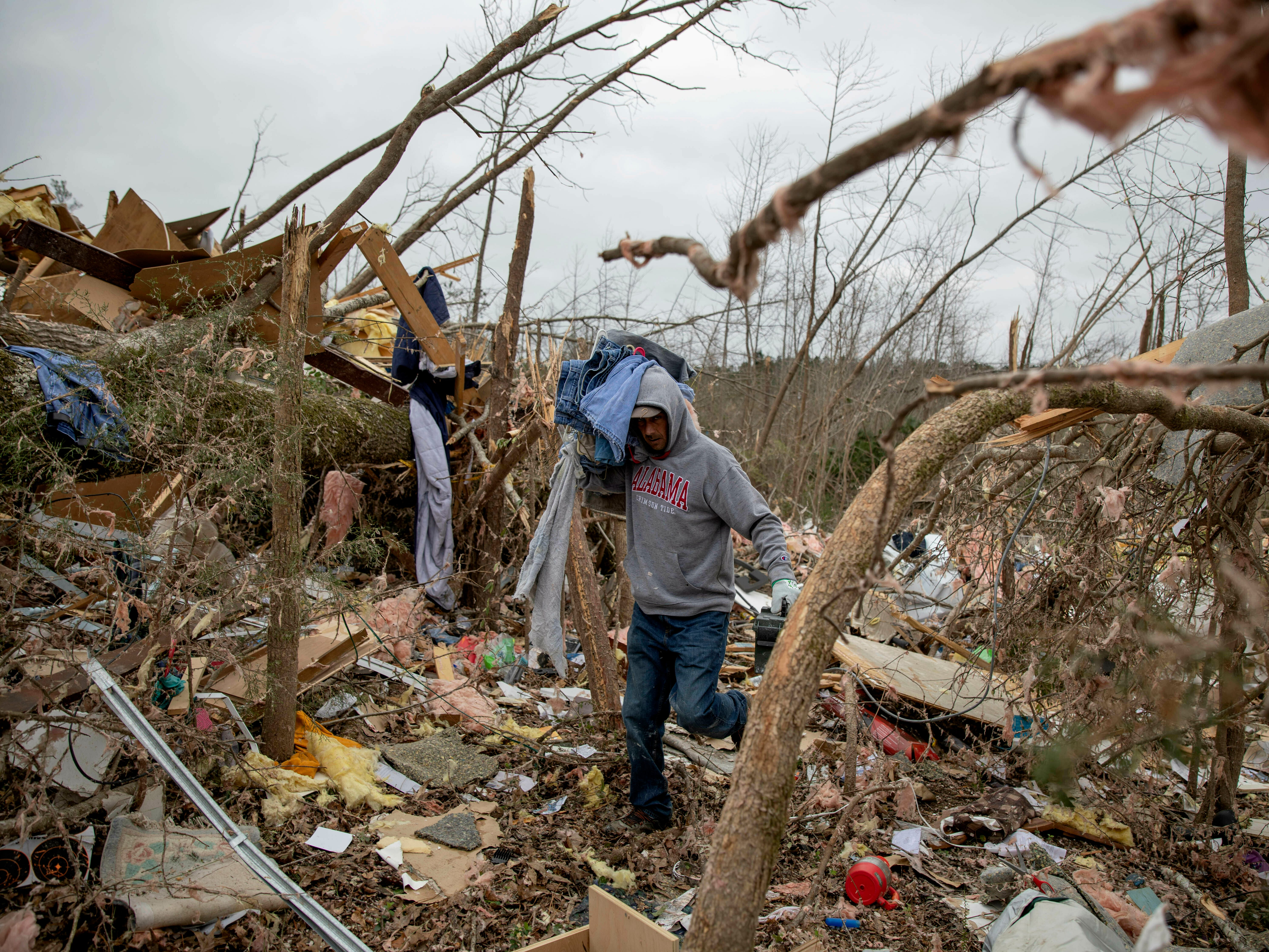 Danny Allen helps recover belongings while sifting through the debris of a friend's home destroyed by a tornado in Beauregard, Ala., March 4, 2019.