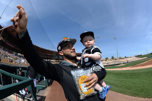 March 4: White Sox 3B Yolmer Sanchez brings 1-year-old Lucas Schatz of Chicago onto the field.