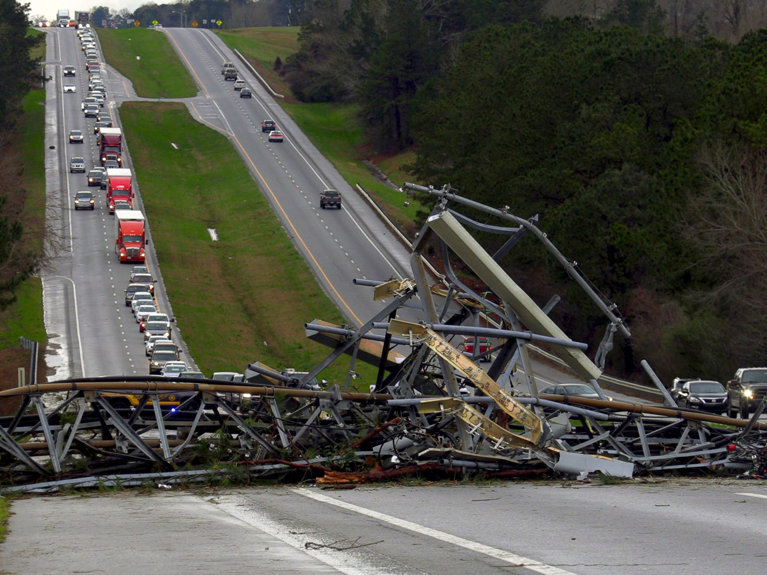 A fallen cell tower lies across U.S. Route 280 highway in Lee County, Ala., in the Smiths Station community after what appeared to be a tornado struck in the area Sunday, March 3, 2019. Severe storms destroyed mobile homes, snapped trees and left a trail of destruction amid weather warnings extending into Georgia, Florida and South Carolina, authorities said. (Mike Haskey/Ledger-Enquirer via AP) ORG XMIT: GACOL701