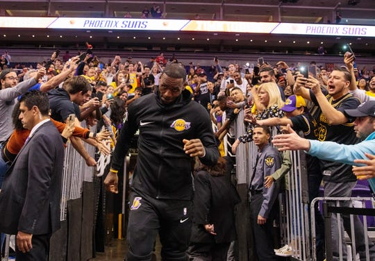Fans react as the Lakers' LeBron James runs past them at Talking Stick Resort Arena before a game against the Suns.