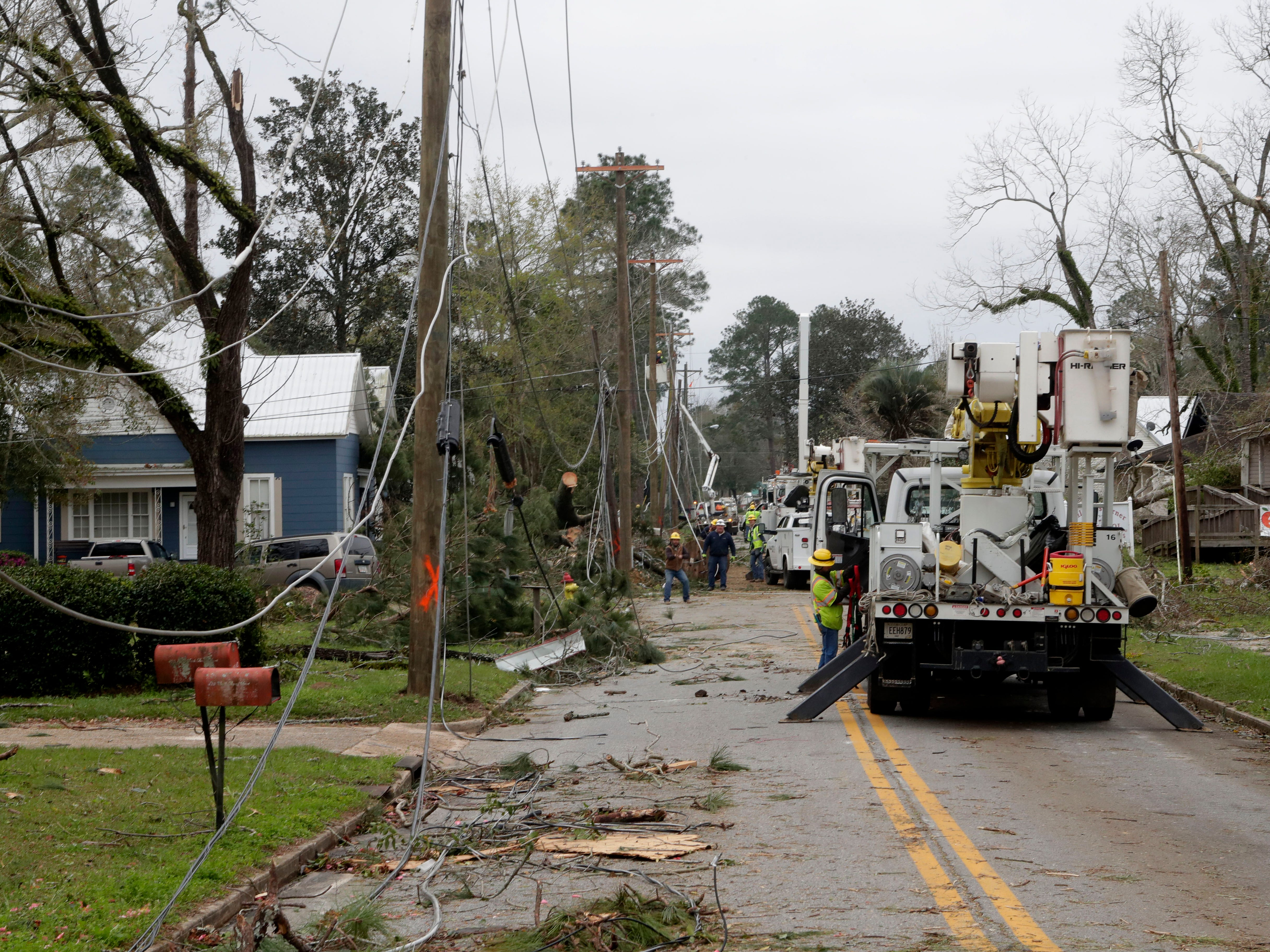 Crews work to clean up debris and fallen power lines in Cairo, Ga. on March 4, 2019.
