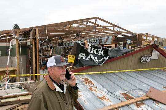 David McBride, owner of Buck Wild Saloon, talks on the phone in front of his bar after it was destroyed by a tornado  March 4, 2019 in Smith Station, Ala.  While no customers were inside, McBride was sitting in his truck outside of the bar when the tornado hit Sunday afternoon.