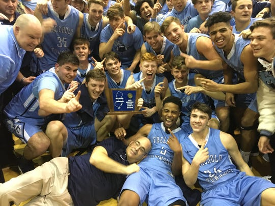 Freehold Township's basketball players celebrate the program's first sectional title with longtime head coach Brian Golub (bottom).