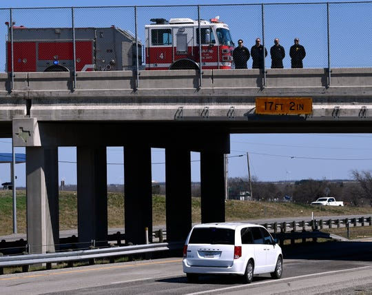 Abilene Fire Department firefighters stand on the West Lake Road overpass over Interstate 20 as the body of slain Midland police officer Nathan Heidelberg was taken Tuesday to Fort Work. Heidelberg had been killed earlier in the day responding to an alarm at a residence, his body was being taken to Tarrant County for an autopsy.