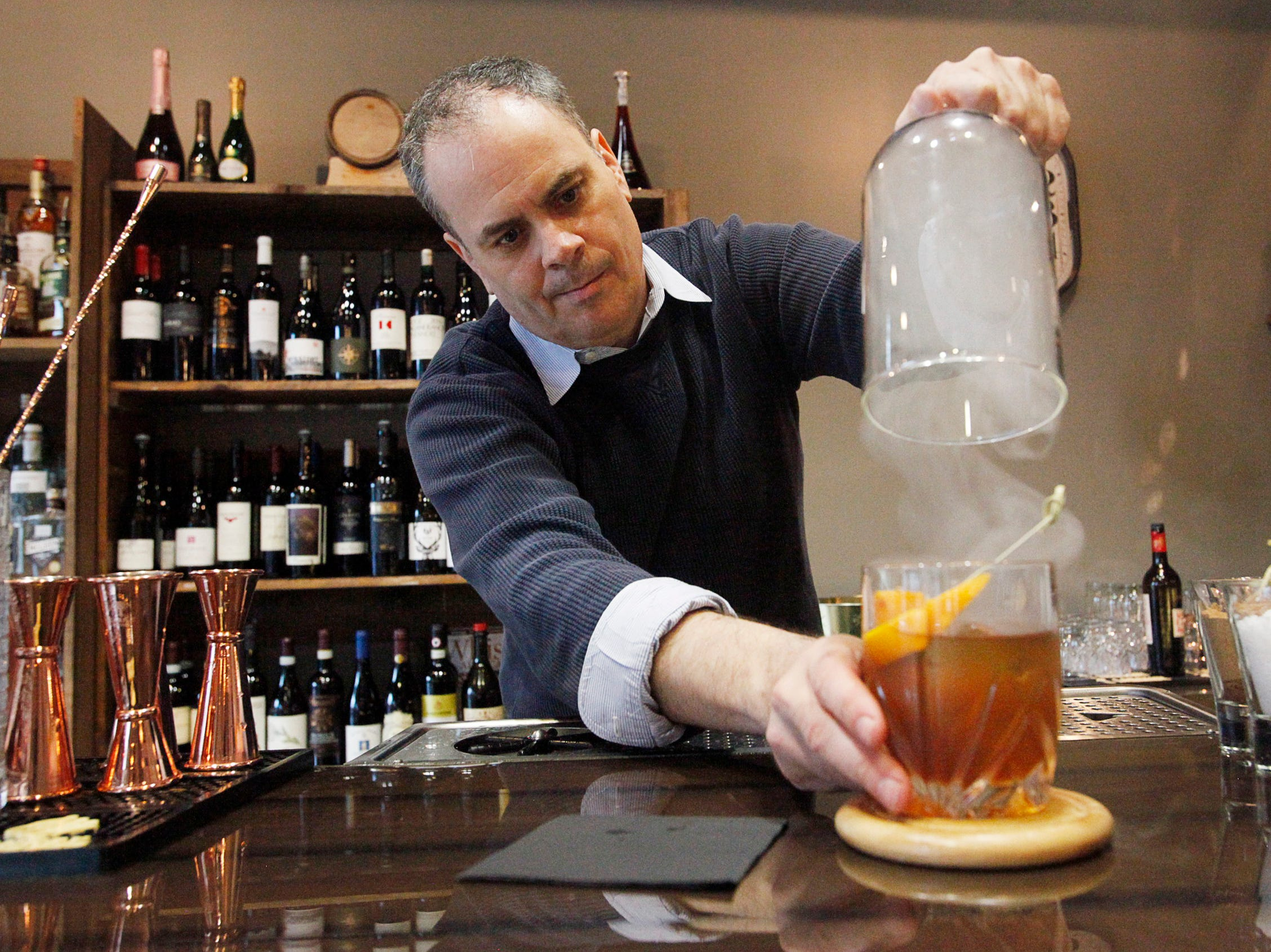 A Smoking Gun cocktail is infused withhickory smokeunder a glass dome at Monk's Flask March 1, 2019.