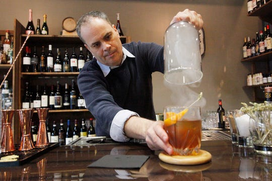 A Smoking Gun cocktail is infused with hickory smoke under a glass dome at Monk's Flask March 1, 2019.