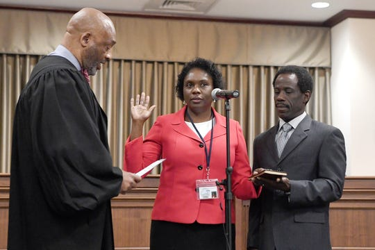 Chief District Court Judge Calvin Hill officially swears Avril Pinder, standing with her husband, Ellis, in as the new Buncombe County manager on March 5, 2019.