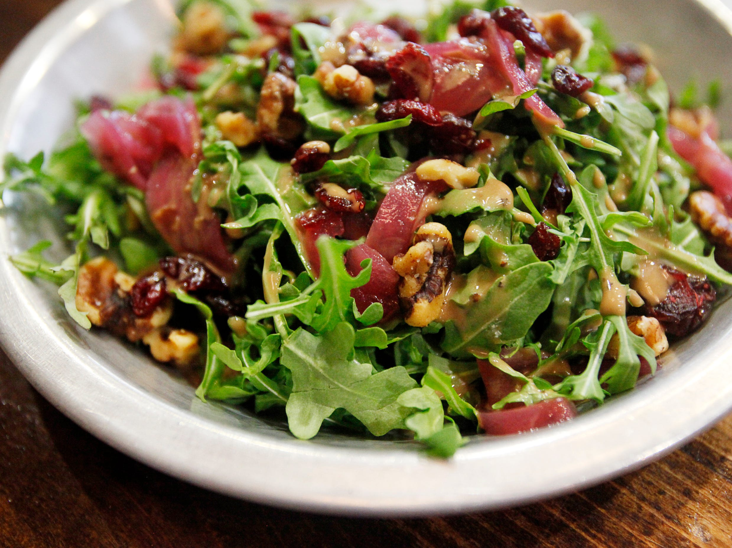 The Monk's Flask house salad comes with arugula, pickled red onion, dried cranberries and toasted walnuts with a basic balsamic vinaigrette.