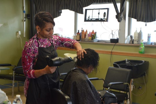 Crystal Hall (left), owner of Cute & Sassy Salon at 243 North Ave., works on a client's hair.