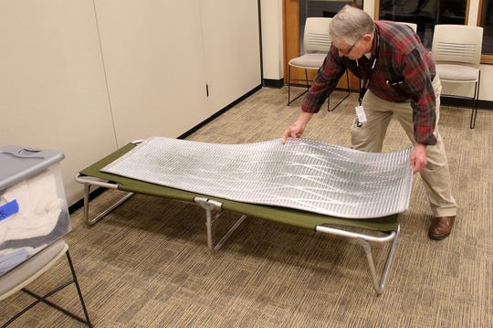 Kingston severe weather shelter volunteer Jon Geisbush arranges a cot in the Village Green Community Center on Monday, March 4, 2019.