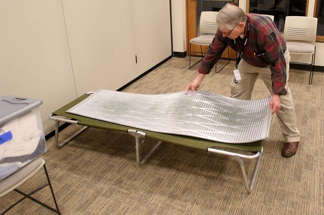 Kingston severe weather shelter volunteer Jon Geisbush arranges a cot in the Village Green Community Center in March.