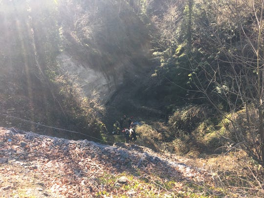 Fire crews and police help load a 29-year-old man, found near-naked in a creek 100 feet down a ravine, into a basket.