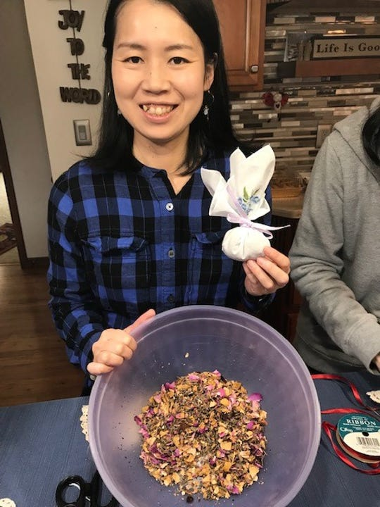 Nozomi Akatsuka, member of the Rising Sun Friends, completed a handkerchief sachet using a small amount of potpourri from the blend in her bowl.