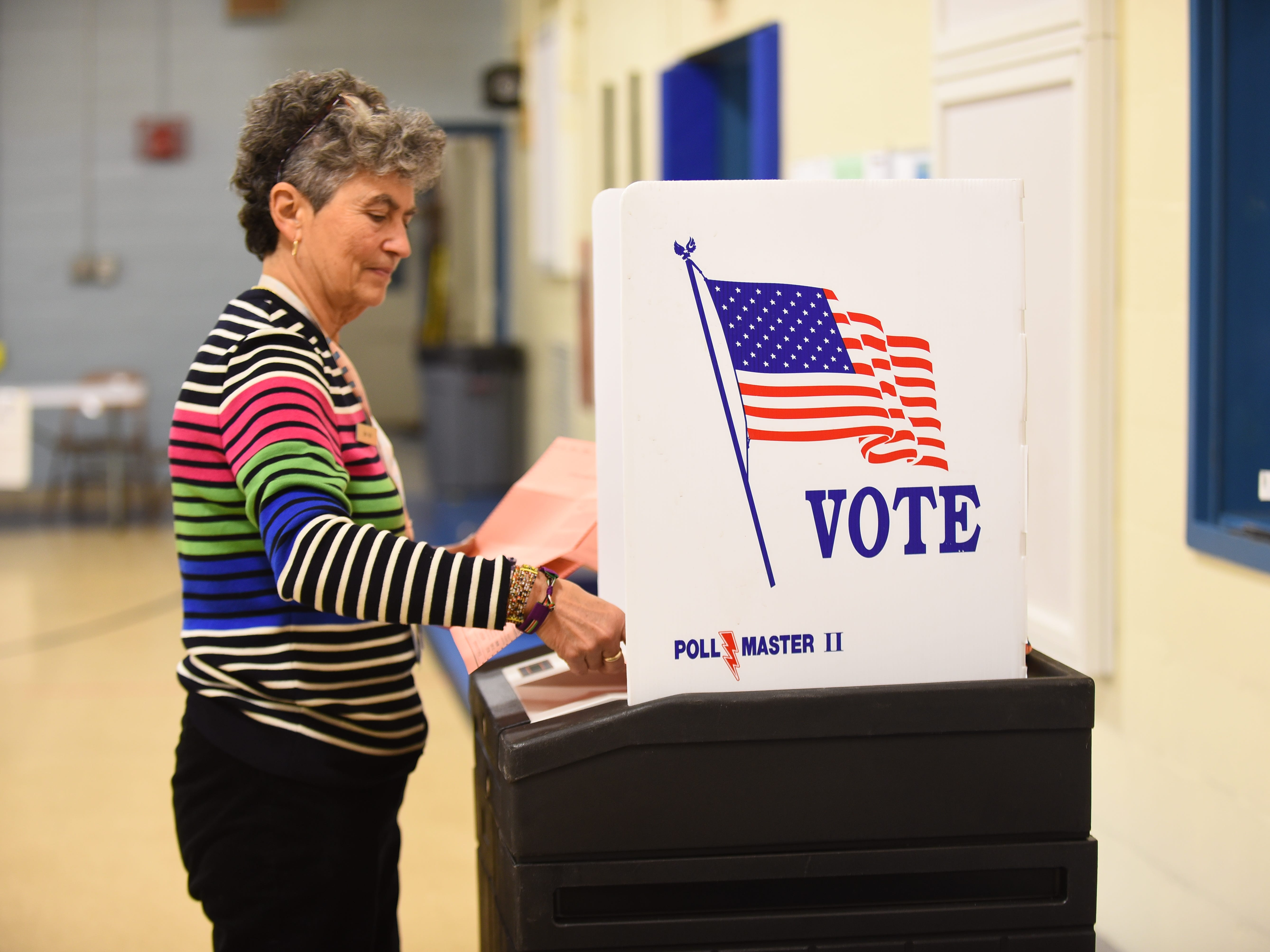 Lynn Vera, a member of the South Burlington Board of Civil Authority, enters mailed-in ballots into the counting machine on Town Meeting Day, Tuesday March 5, 2019, at Orchard School in South Burlington.