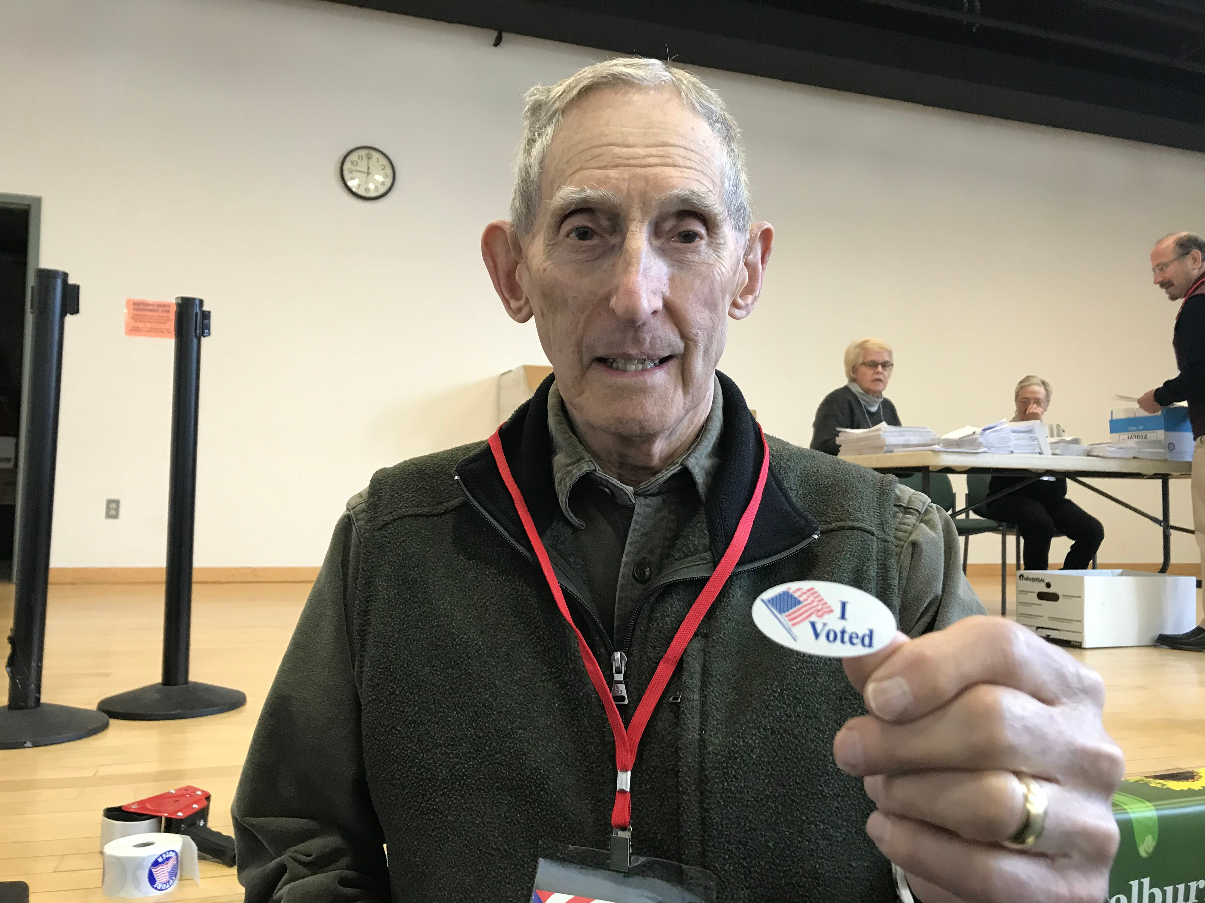 """Bud Ockert, 83, a lifelong Shelburne resident and a fixture at on Town Meeting Day, gives out """"I voted"""" stickers after guiding residents to insert ballots into the machine for tallying. Seen on Tuesday, March 5, 2019."""