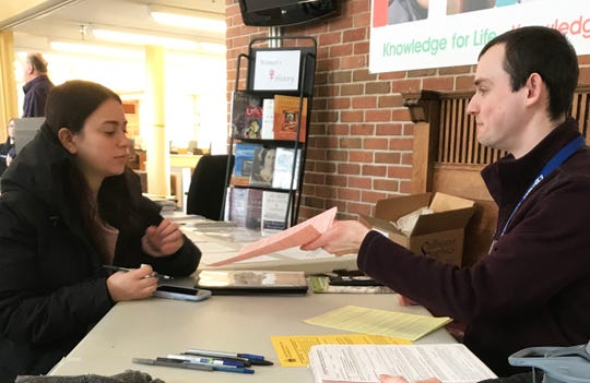 Matt Walasewicz, right, completes voter registration for Liane Bluth at Fletcher Free Library, where she will cast her vote March 5, 2019.