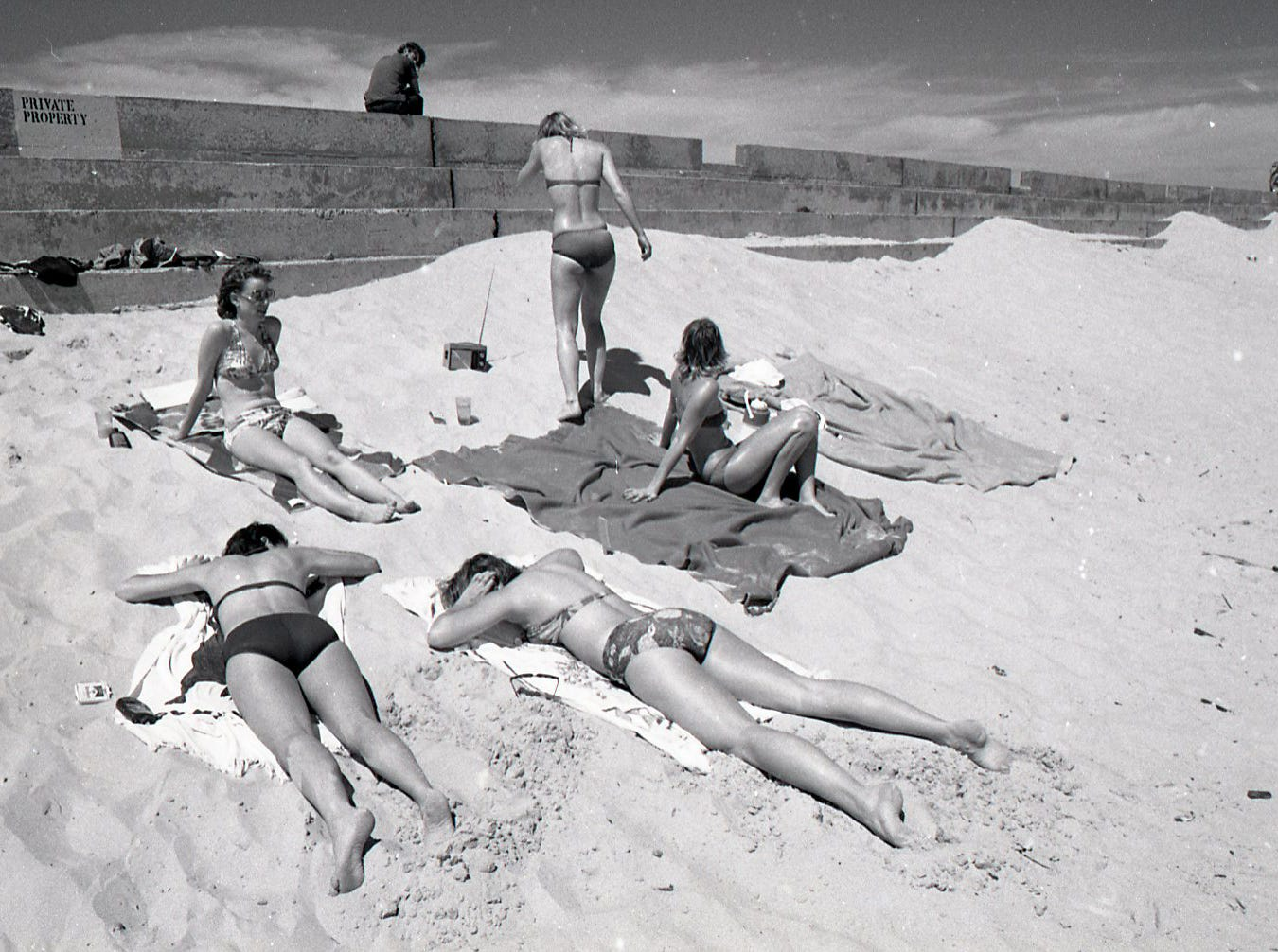 Spring breakers sun bathing in front of the Padre Island seawall on March 18, 1978.