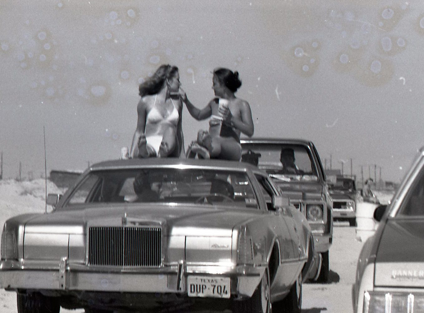 Two spring breakers hitch a ride on top of a car on March 18, 1978 on Padre Island.